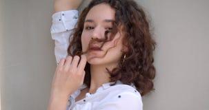 Ritratto del primo piano di giovane modello femminile caucasico riccio dai capelli lunghi grazioso che esamina macchina fotografi video d archivio