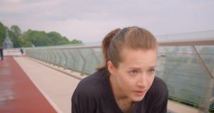 Ritratto del primo piano di giovane pareggiatore femminile sportivo caucasico in una maglietta nera che corre sul ponte in città  stock footage