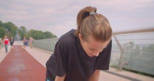 Ritratto del primo piano di giovane pareggiatore femminile sportivo caucasico in una maglietta nera che ottiene motivata e che in stock footage