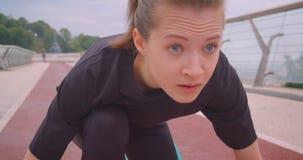 Ritratto del primo piano di giovane pareggiatore femminile sportivo caucasico in una maglietta nera che si siede in una posizione archivi video