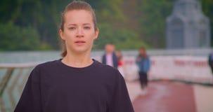 Ritratto del primo piano di giovane pareggiatore femminile sportivo grazioso in una maglietta nera che corre sul ponte in città u stock footage