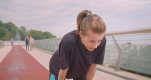 Ritratto del primo piano di giovane pareggiatore femminile sportivo sveglio in una maglietta nera che ottiene motivata e che iniz stock footage