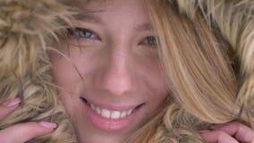 Ritratto del primo piano di giovane ragazza caucasica sveglia che si nasconde in cappuccio della pelliccia meravigliosamente che  stock footage