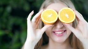 Ritratto del primo piano di giovane ragazza divertente che posa con le metà delle arance sugli occhi che esaminano macchina fotog archivi video