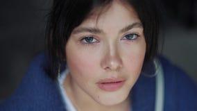 Ritratto del primo piano di giovane ragazza triste con gli occhi blu-marroni sbalorditivi archivi video