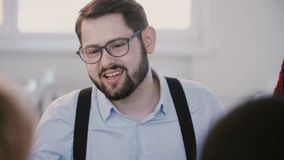 Ritratto del primo piano di giovane riuscito uomo d'affari bello che sorride, parlante alla riunione sana moderna dell'ufficio de stock footage