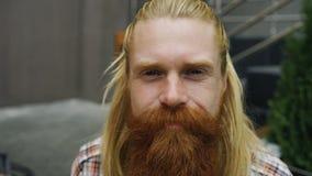 Ritratto del primo piano di giovane sorridere barbuto dell'uomo felice e di esaminare macchina fotografica Fotografia Stock