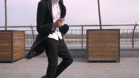 Ritratto del primo piano di giovane sorridere di camminata e ballante afroamericano attraente felice dell'uomo d'affari sulla via video d archivio
