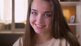 Ritratto del primo piano di giovane sorridere femminile caucasico attraente macchina fotografica felicemente di sguardo all'inter stock footage