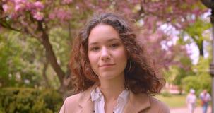 Ritratto del primo piano di giovane sorridere femminile caucasico riccio dai capelli lunghi macchina fotografica felicemente di s archivi video