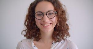 Ritratto del primo piano di giovane sorridere femminile caucasico riccio dai capelli lunghi sveglio felicemente riparando i suoi  stock footage