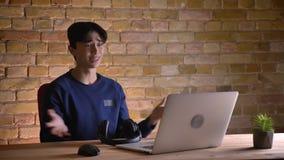 Ritratto del primo piano di giovane studente maschio coreano attraente in cuffie che verifica il computer portatile e che ottiene archivi video