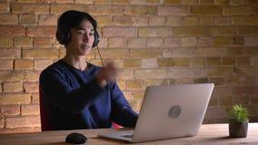 Ritratto del primo piano di giovane studente maschio coreano attraente nelle cuffie che hanno una video chiamata sul computer por stock footage