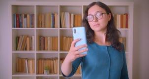 Ritratto del primo piano di giovane studentessa caucasica graziosa in vetri che prendono i selfies sul telefono nella biblioteca  archivi video