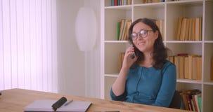 Ritratto del primo piano di giovane studentessa caucasica graziosa in vetri che studia e che ha una telefonata che parla allegram archivi video