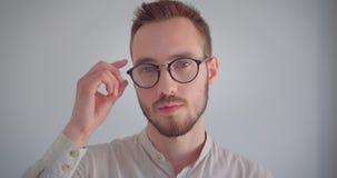 Ritratto del primo piano di giovane uomo attraente in vetri che esaminano macchina fotografica con fondo isolato stock footage