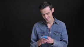 Ritratto del primo piano di giovane uomo caucasico che passa in rassegna sul telefono e che sorride davanti alla macchina fotogra stock footage