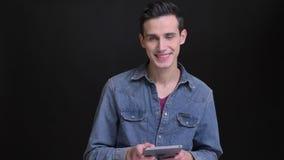 Ritratto del primo piano di giovane uomo caucasico facendo uso della compressa poi che esamina macchina fotografica e che sorride stock footage
