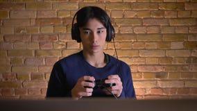 Ritratto del primo piano di giovane uomo coreano attraente in cuffie che giocano i video giochi e conquista video d archivio