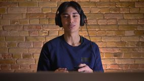 Ritratto del primo piano di giovane uomo coreano attraente in cuffie che giocano i video giochi e che vengono a mancare il livell stock footage