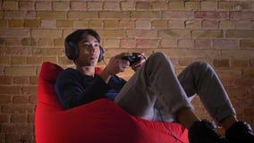 Ritratto del primo piano di giovane uomo coreano che gioca i video giochi facendo uso della console che ottiene conquista felice  video d archivio