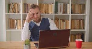 Ritratto del primo piano di giovane uomo d'affari caucasico che scrive sul computer portatile che è premuroso nell'ufficio all'in stock footage