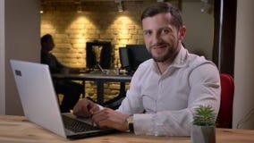 Ritratto del primo piano di giovane uomo d'affari caucasico che si siede davanti al computer portatile che esamina macchina fotog archivi video