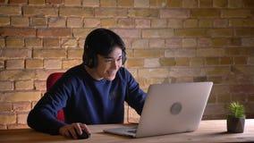 Ritratto del primo piano di giovane uomo d'affari coreano attraente in cuffie facendo uso del computer portatile e di risata con  video d archivio