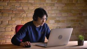 Ritratto del primo piano di giovane uomo d'affari coreano in cuffie che passa in rassegna sul computer portatile e che si eccita  archivi video