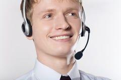 Ritratto del primo piano di giovane uomo sorridente di affari con la cuffia avricolare Fotografia Stock Libera da Diritti