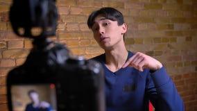 Ritratto del primo piano di giovane videoblogger maschio coreano che gesturing dire di colpire i simili per basare e sottoscriver stock footage