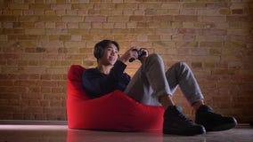 Ritratto del primo piano di giovane videoblogger maschio coreano che gioca i video giochi online che si siedono nella borsa di fa stock footage