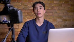Ritratto del primo piano di giovane videoblogger maschio coreano che parla sul ciao d'ondeggiamento della macchina fotografica co stock footage