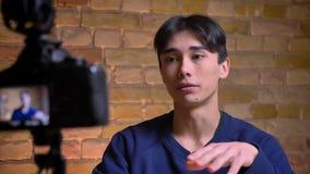 Ritratto del primo piano di giovane videoblogger maschio coreano che parla sulla macchina fotografica e sul gesturing video d archivio