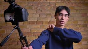 Ritratto del primo piano di giovane videoblogger maschio coreano che parla sulla macchina fotografica che gesturing e che mostra  video d archivio