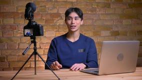 Ritratto del primo piano di giovane videoblogger maschio coreano che parla sulla macchina fotografica che gesturing e che precisa video d archivio