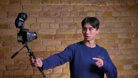 Ritratto del primo piano di giovane videoblogger maschio coreano che tiene macchina fotografica e che mostra qualcosa lui all'int video d archivio