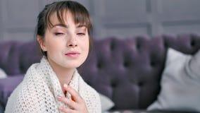 Ritratto del primo piano di godere romantico timido della donna avvolto in plaid tricottato caldo in salone archivi video