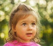 Ritratto del primo piano di piccola ragazza sveglia che guarda con l'interesse nel fondo brillante Fotografia Stock Libera da Diritti