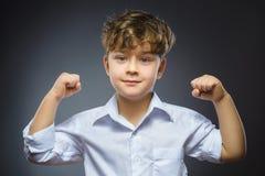 Ritratto del primo piano di piccolo bambino divertente mostra dei suoi muscoli del bicipite della mano Il forte bambino serio che immagini stock libere da diritti