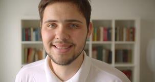 Ritratto del primo piano di sorridere maschio caucasico bello macchina fotografica allegramente di sguardo nella biblioteca con g