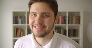 Ritratto del primo piano di sorridere maschio caucasico bello macchina fotografica felicemente di sguardo nella biblioteca con gl