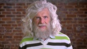 Ritratto del primo piano di stupore del nonno caucasico con la grande barba bianca ed i capelli ricci, studin moderno del mattone video d archivio