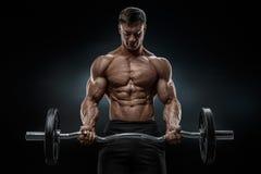 Ritratto del primo piano di un allenamento muscolare dell'uomo con il bilanciere alla palestra