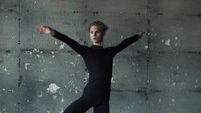 Ritratto del primo piano di un ballerino di balletto maschio su un fondo scuro dancing del giovane nello studio Movimento lento stock footage