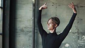Ritratto del primo piano di un ballerino di balletto maschio su un fondo scuro Movimento lento video d archivio
