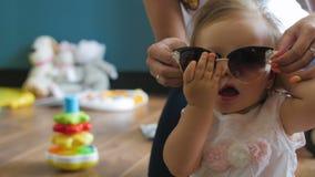Ritratto del primo piano di un bambino sveglio felice della bambina con gli occhiali da sole video d archivio
