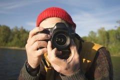 Ritratto del primo piano di un uomo che prende un'immagine con la macchina fotografica professionale della foto su un lago fotografia stock libera da diritti