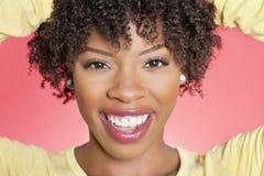 Ritratto del primo piano di una donna afroamericana che sorride sopra il fondo colorato immagini stock