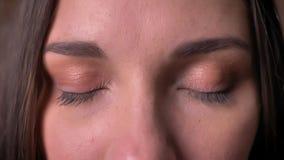 Ritratto del primo piano di una donna, che guarda nella macchina fotografica e chiude i suoi occhi stock footage